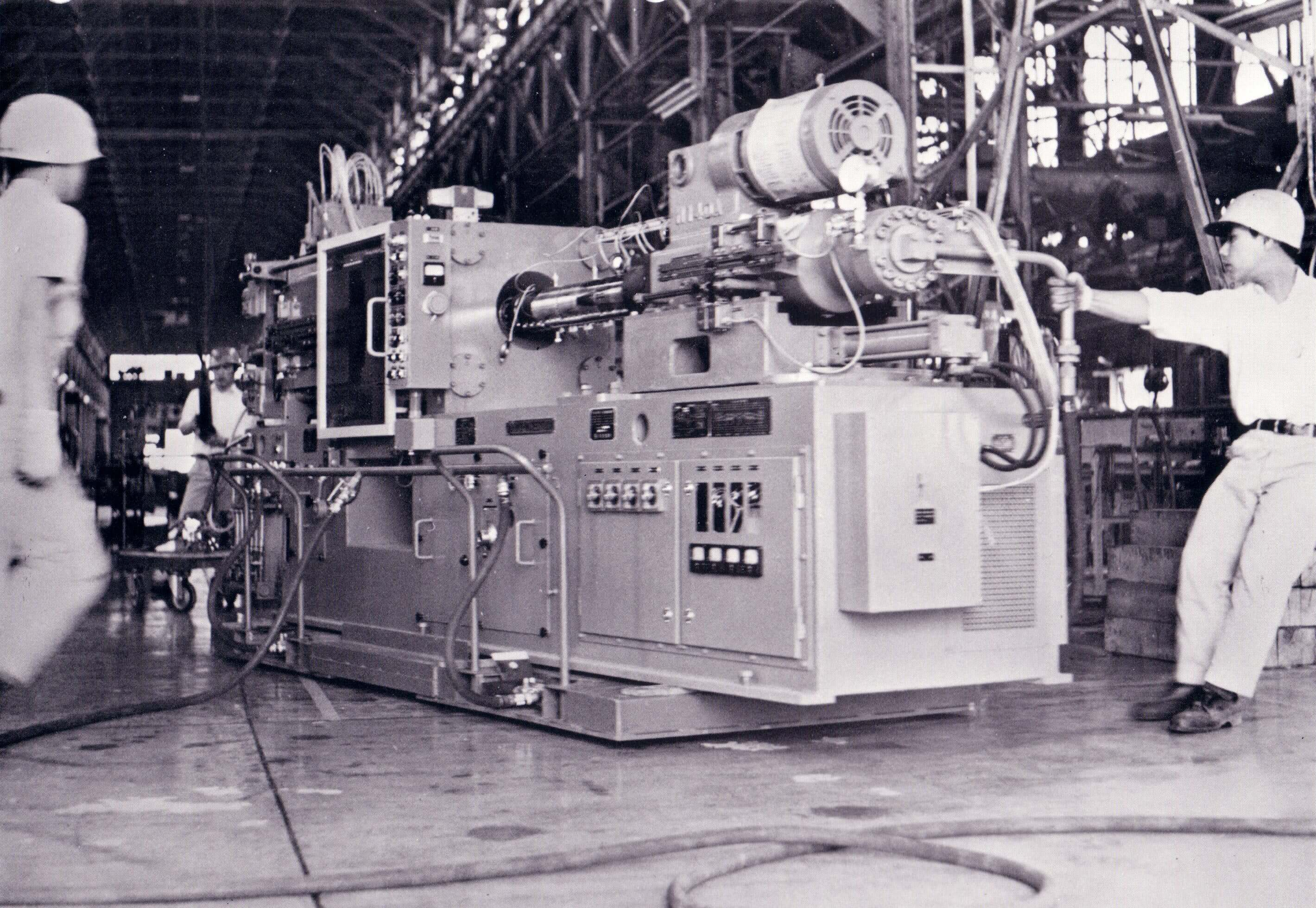 1960s factory workers moving heavy machine with air bearings