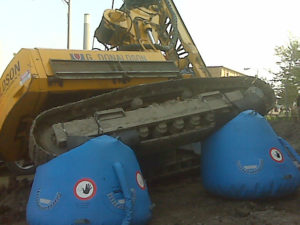 Landing bags supporting an excavator underneath treads